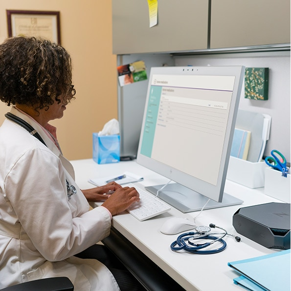 doctor sitting at desk looking at the HP HEALTHCARE EDITION HC270CR CLINICAL REVIEW DISPLAY