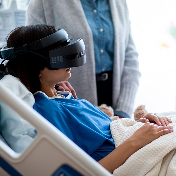 young patient in bed wearing HP mixed reality headset