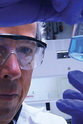 Scientist with blue gloves and googles looking to a blue liquid in a sample tube