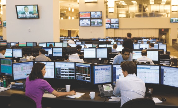 Man and woman working at desks with workstation monitors on a financial trading floor