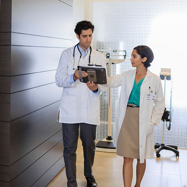 two doctors standing looking at a mobile device