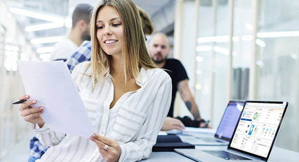 Woman looking at paperwork next to a monitor showing HP PrintOS
