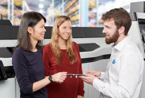 Two women and a man standing in front of an HP Jet Fusion color 3D printer looking at 3D printed part