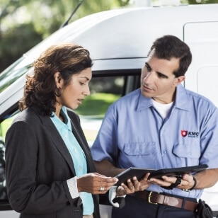 Delivery man standing next to a women using HP product to confirm delivery