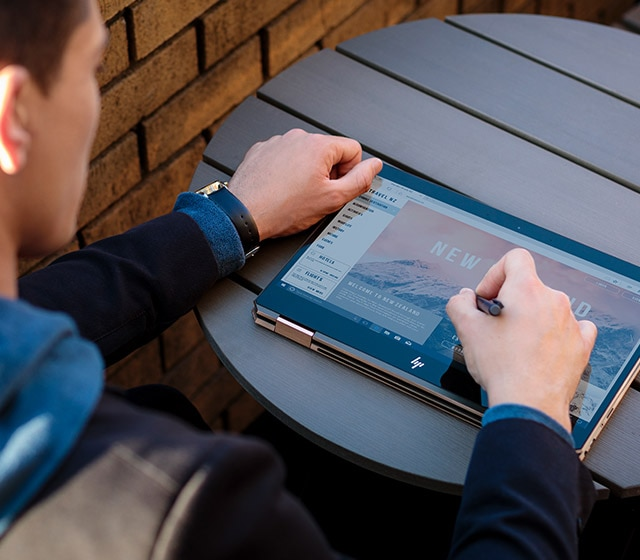 Man using digital pen laptop in tablet mode outside on a table