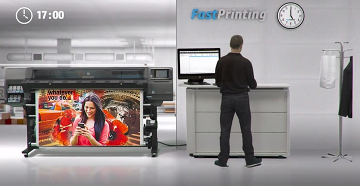Man at a print shop with HP Latex printer with colorful output