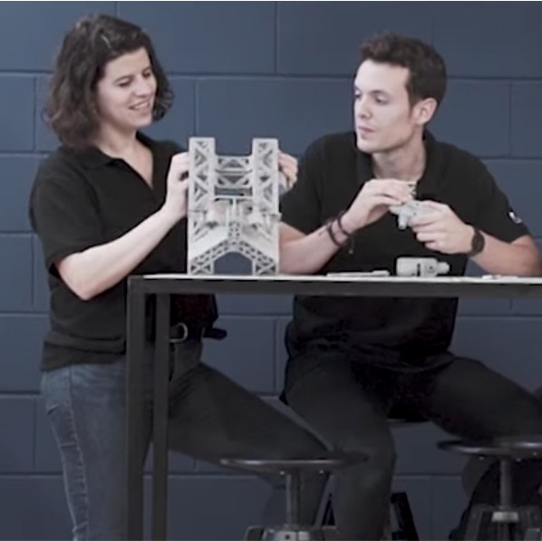 Man and woman at a table facing camera reviewing 3D printed parts