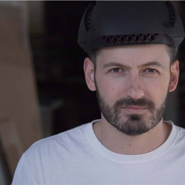 Man looking into camera wearing 3D printed sports helmet