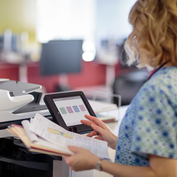 nurse using an HP multi-function printer in a hospital setting