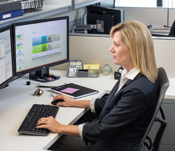 Woman working on HP Dual Monitors and HP Zero Client