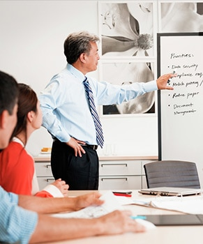 man pointing to a board and 2 people sitting down at a meeting table