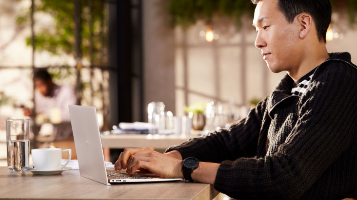 Man working with an HP ENVY Laptop over a desk - left view