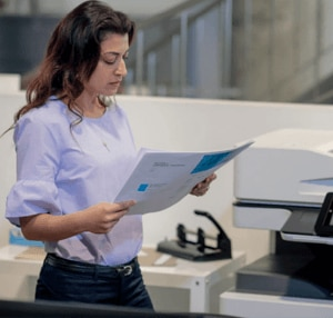 Business woman picking up and reviewing prnted document from HP A3 Copier