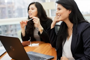 two women smiling during an office meeting in front of an HP laptop