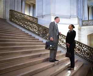 Image of man and woman talking on marble staircase